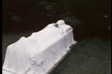 Tombstone in the shape of a woman sleeping on a bed holding flowers — Stockvideo
