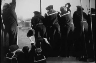 Rear view of sailors waving to submarine