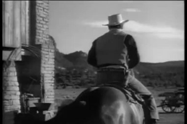 Rear view of cowboy riding towards mountains — Stock Video #26665417