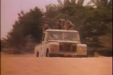 Soldiers shooting from military jeep