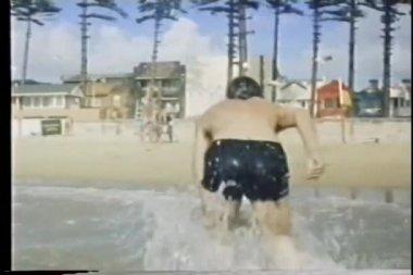вид сзади человека вылезая из воды и ходить на пляж — Стоковое видео