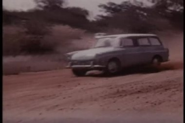 Two cars skidding off dirt road