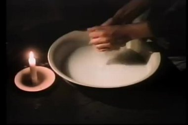 Close-up of hands wringing out rag in basin by candle light — Stock Video