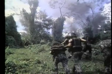 Rear view of troops running up hill toward smoke — Stok video