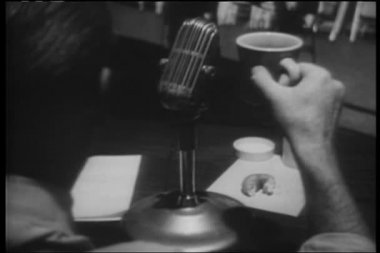 Rear view of radio announcer with coffee and donut — Stock Video