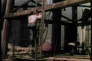 Pan up man climbing ladder on side of derrick at oil refinery — Wideo stockowe