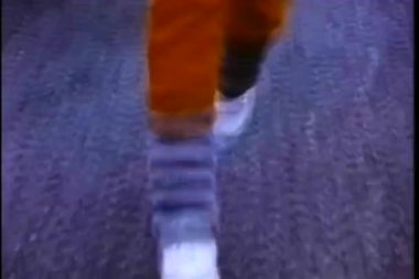 Close-up of person jogging in sneakers and leg warmers — Стоковое видео