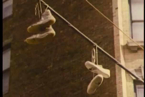 Espadrilles suspendus de la pole position dans la rue — Vidéo