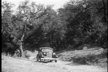 Car driving down narrow country road — Wideo stockowe