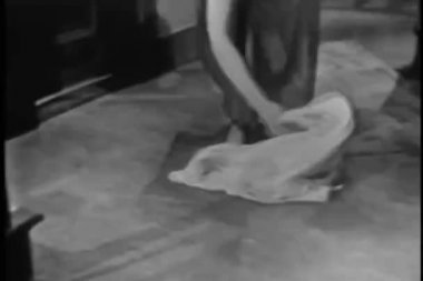 Woman picking up clothing from floor — Stok video