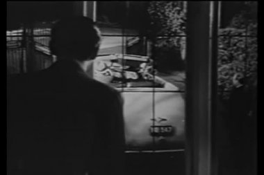 Man looking out window at people leaving in car — Wideo stockowe