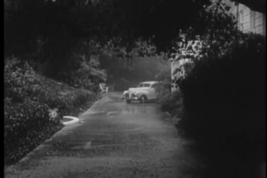 1940s car stopping on side of house in the rain — Vídeo de stock