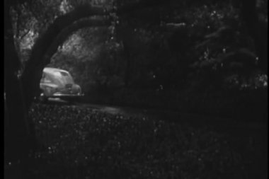 Car driving up road to house in the rain, 1940s — Stock Video