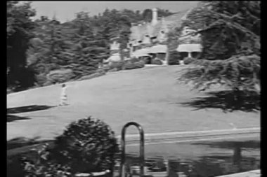Woman running across lawn towards mansion — Vídeo Stock