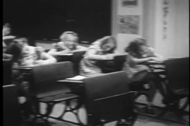 Children getting up from their desks in classroom — Stockvideo
