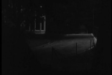 Three men running across front lawn of large house at night — ストックビデオ