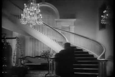 Woman in evening gown walking up grand staircase — Video Stock