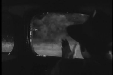 Man inside car wiping window during rain storm — Stockvideo
