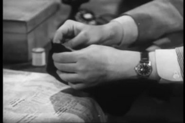 Man darning sock at table — Stockvideo
