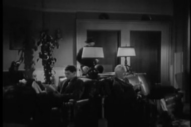 People waiting in lobby of hotel, 1940s — Stok video