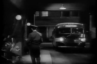 Bus entering terminal at night — Wideo stockowe