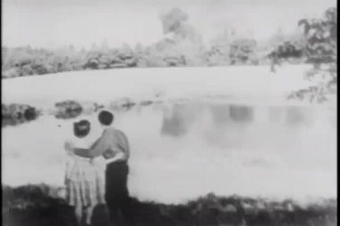 Couple watching forest fire from across pond — Wideo stockowe