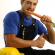 Young worker eating carrot — Foto de Stock