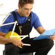 Young worker reading instructions - Stock Photo