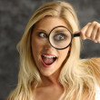 Blonde girl with a magnifying glass — Stock Photo