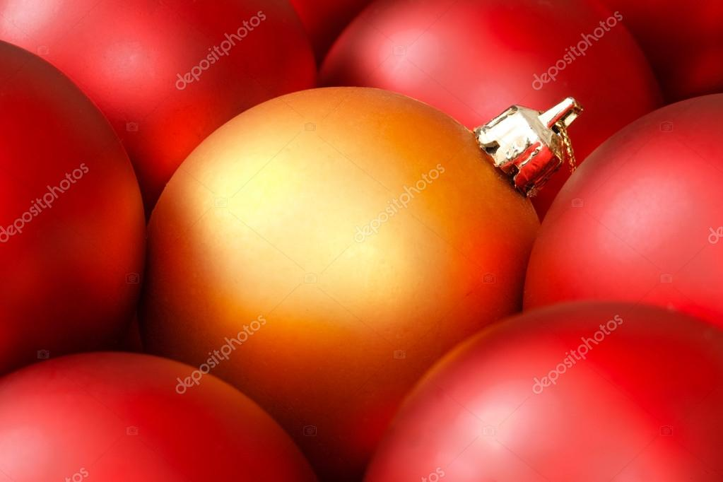 Golden christmas bauble surrounded by red ornaments — Stock Photo #13129237
