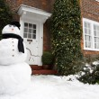 Snowman and house — Stock Photo