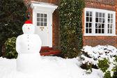 Snowman outside house — Stock Photo