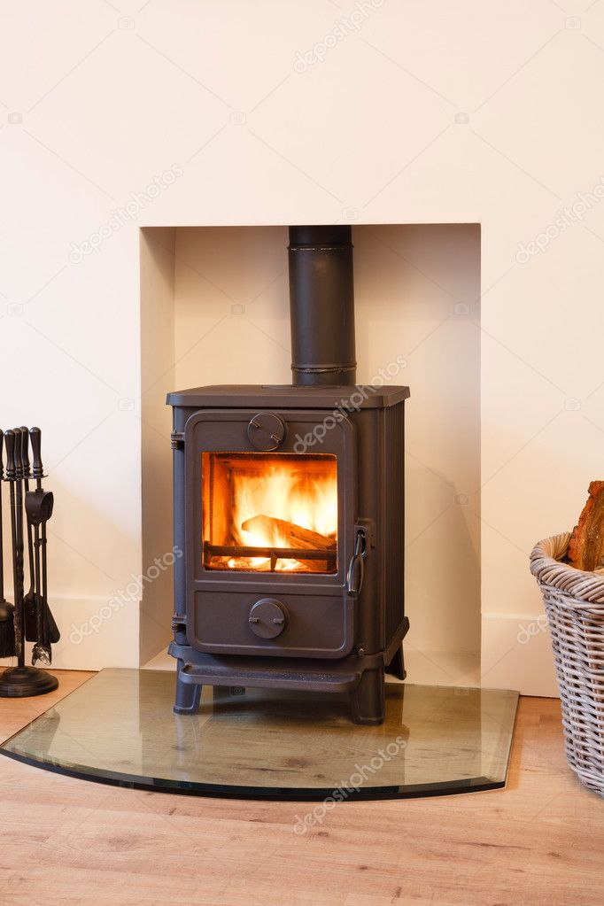 Cast iron wood burning stove in a modern contemporary fireplace  Stock Photo #13203858