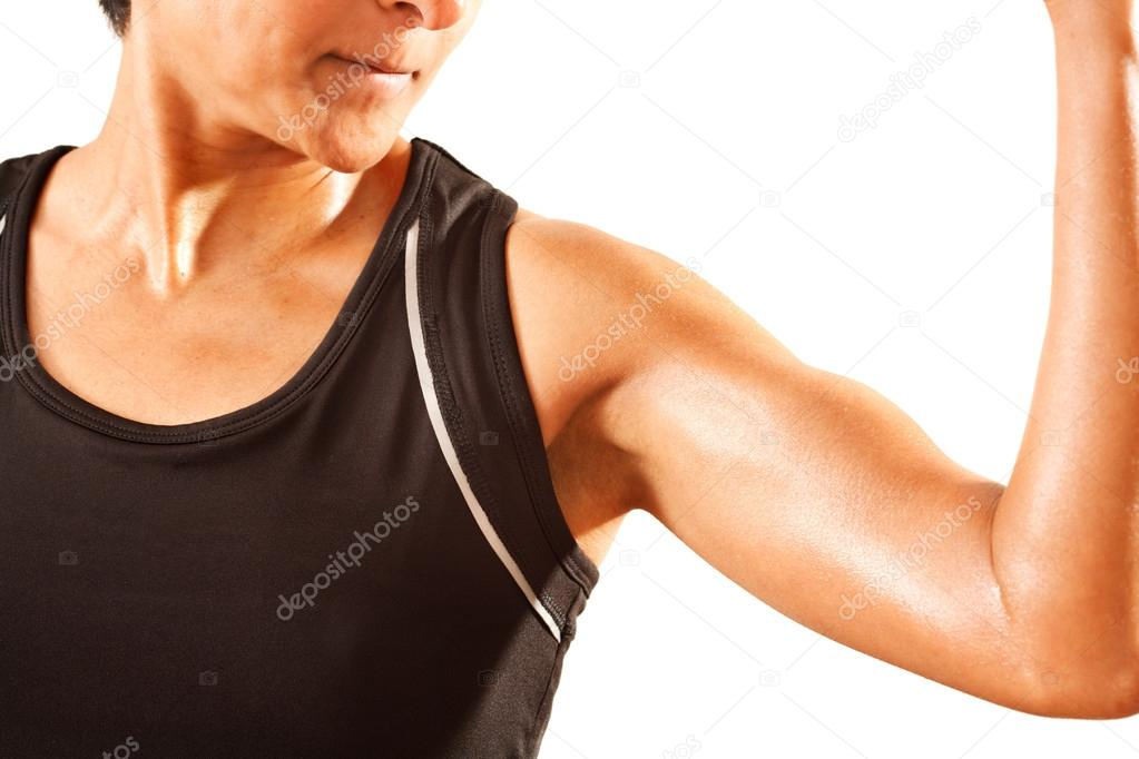 An athletic Asian Indian woman clenches her bicep. White background.  Stock Photo #13204300