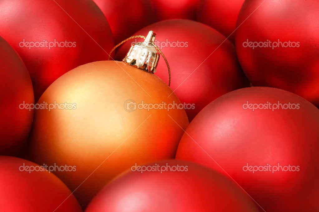 Gold christmas bauble amongst red ornaments — Stock Photo #13276128