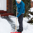 Woman with snow shovel — Stock Photo