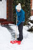 Woman with snow shovel — Stock Photo
