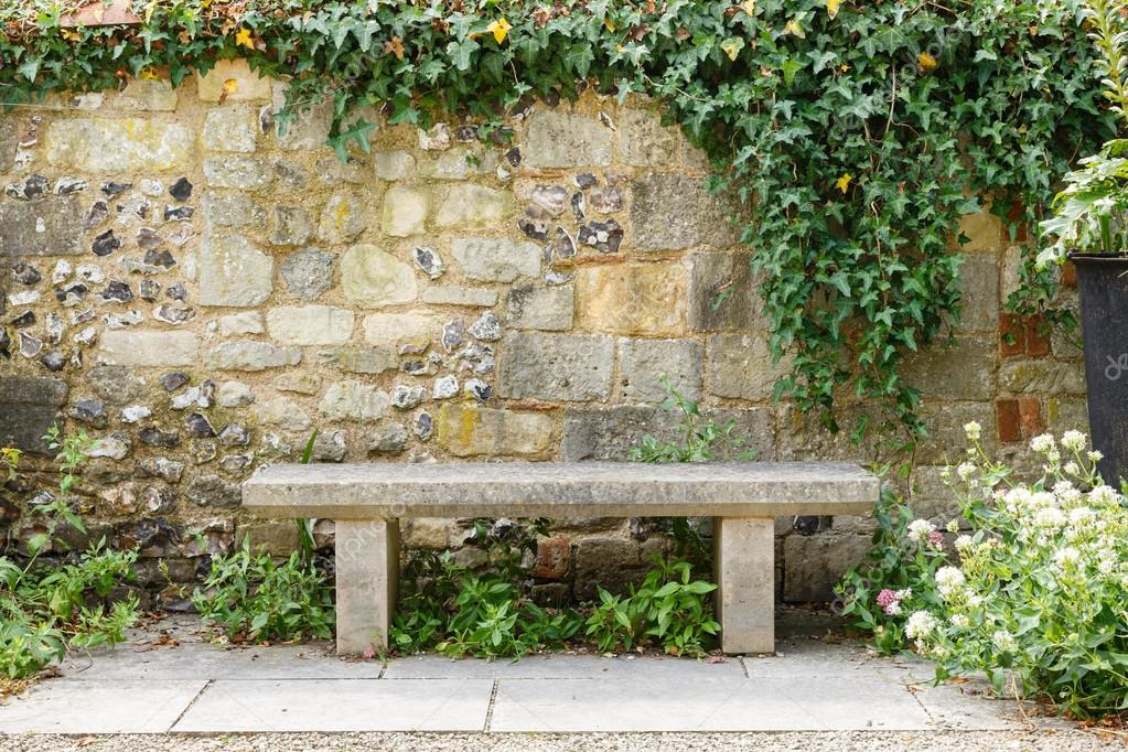 Bench in a formal garden with an old stone wall — Stock Photo #18886673