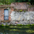 Old stone wall on river - Foto Stock