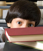 Boy behind books — Stockfoto