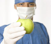 Doctor holding a green apple — Stock Photo