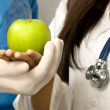 Two doctors holding green apple — Stock Photo #13920070