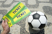 Soccer fan holds tickets above football in Brazil — Stock Photo