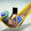 Brazilian Man Relaxes Using Tablet in Hammock on Beach — Stock Photo