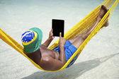 Brazilian Man Relaxes Using Tablet in Hammock on Beach — Stock Photo
