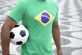 Jogador de futebol brasileiro na camisa de bandeira do brasil segurando futebol rio — Foto Stock