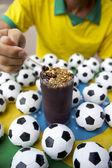 Brazilian Soccer Player Eating Acai with Footballs — Stock Photo