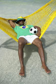 Brazilian Man Relaxing with Soccer Football in Beach Hammock — Stock Photo