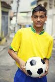 молодой бразильский футболист холдинг футбольный мяч на улице — Стоковое фото
