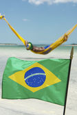 Brazilian Flag Waving in front of Beach Hammocks — Stock Photo